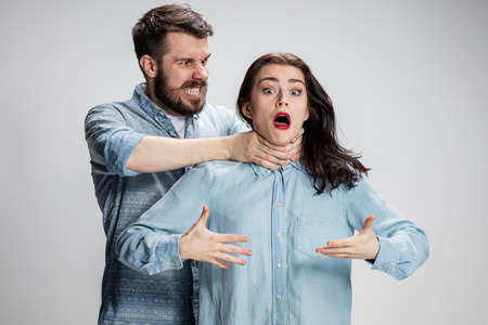 Gli uomini litigare e donne. L'uomo strangolando una donna su sfondo grigio