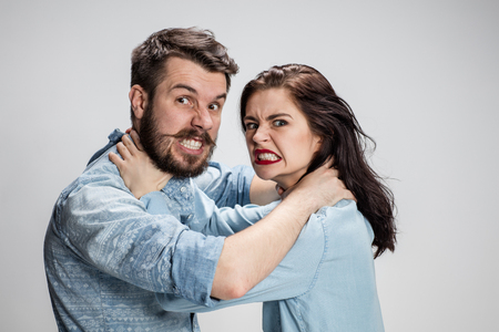 suffocate: The quarrel and strangling man and woman on gray background Stock Photo