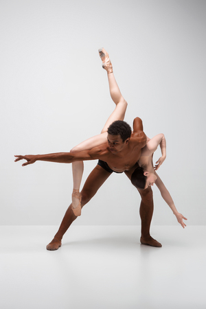 DAnce background: Couple of ballet dancers dancing over gray background