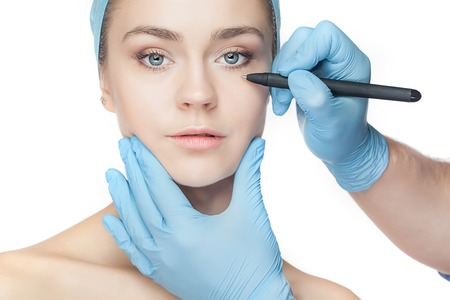 perforation: Beautiful young woman with perforation lines on her face before plastic surgery operation. Beautician touching woman face. Stock Photo