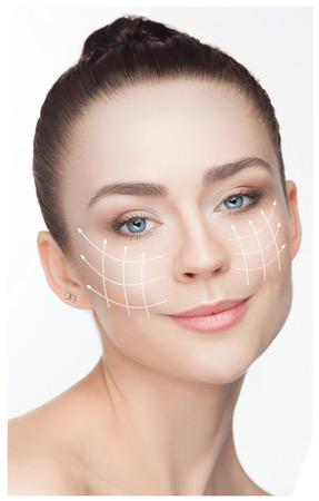 얼굴에 화살표와 함께 아름 다운 젊은 여자. 성형 외과 개념