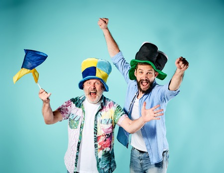 The two football fans with a flag of Ukraine over blue background Stock Photo