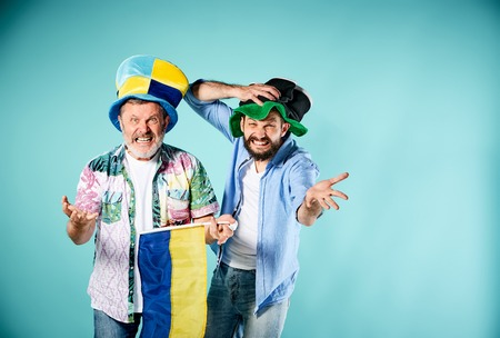 the admirer: The two football fans with a flag of Ukraine over blue background Stock Photo