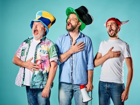 Los tres aficionados al fútbol que cantan el himno nacional sobre fondo azul