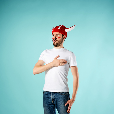 The football fan singing the national anthem over blue background