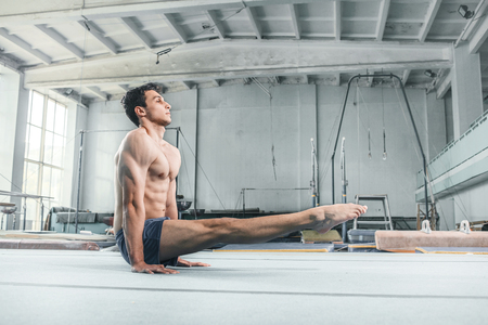 equilibrium: The caucasian man gymnastic acrobatics equilibrium posture at gym background Stock Photo