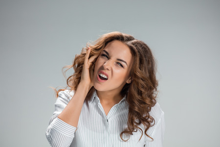 dolor de oido: Una imagen de mujer joven con dolor de oído sobre fondo gris