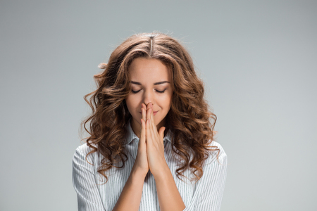 imploring: The Woman is looking imploring over gray background Stock Photo