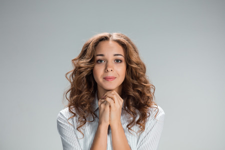 The Woman is looking imploring over gray background Stock Photo