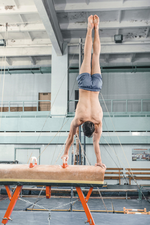 brawny: The sportsman the guy performing difficult exercise, sports gymnastics
