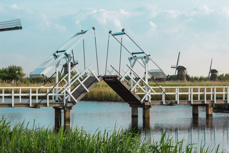 drawbridge: Spring landscape with beautiful traditional dutch windmills near the water channels with drawbridge and reflection in water at sunrise in famous Kinderdijk, Netherlands Stock Photo