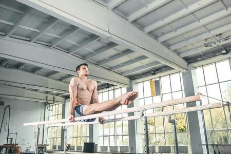 handstand: Male gymnast performing handstand on parallel bars at gym Stock Photo