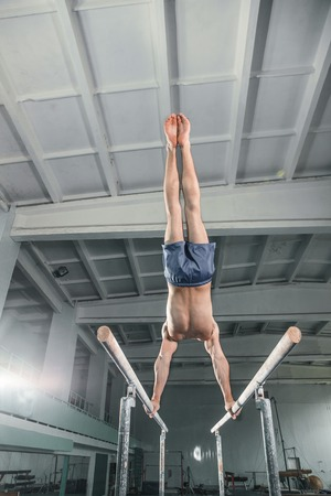gripping bars: Male gymnast performing handstand on parallel bars at gym Stock Photo