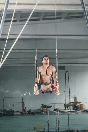 The sportsman performing difficult exercises on on stationary rings, sports gymnastics