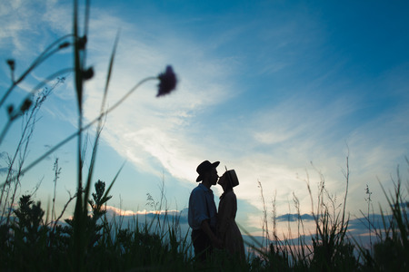 Young couple in love in the meadow against sunset sky. Concept of healthy and rural life
