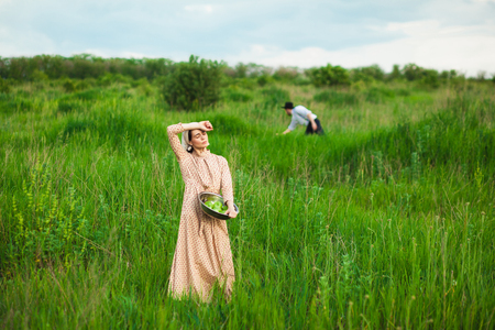 kerchief: The healthy rural life. The woman in kerchief with apples against green meadow