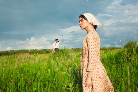 kerchief: The healthy rural life. The woman in kerchief and man in hat against green meadow
