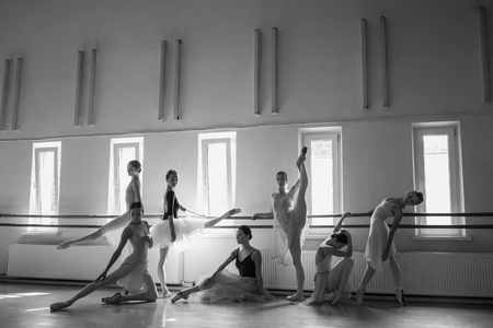 Thr seven ballerinas at ballet rack in the rehearsal hall of the theater. The black and white image Stock fotó