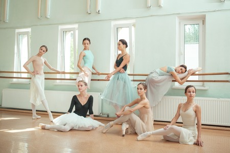adult's feet: Thr seven ballerinas at ballet rack in the rehearsal hall of the theater