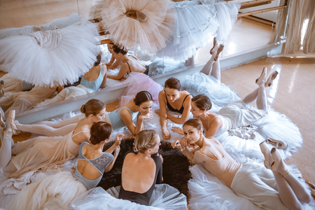 a rehearsal: Thr seven ballerinas lying against ballet rack in the rehearsal hall of the theater