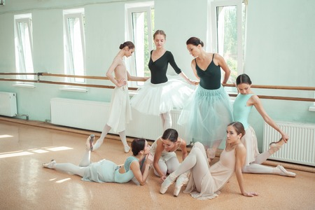 a rehearsal: Thr seven ballerinas at ballet rack in the rehearsal hall of the theater