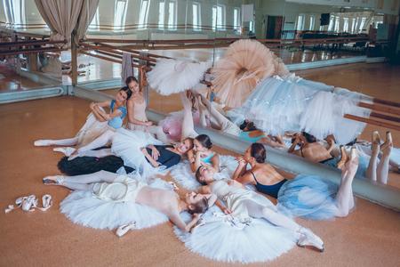 rehearsal: Thr seven ballerinas lying on tatus on floor in the rehearsal hall of the theater Stock Photo
