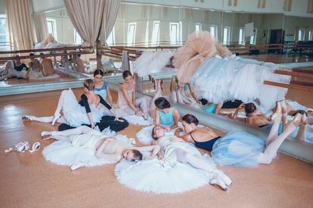 a rehearsal: Thr seven ballerinas lying on tatus on floor in the rehearsal hall of the theater Stock Photo
