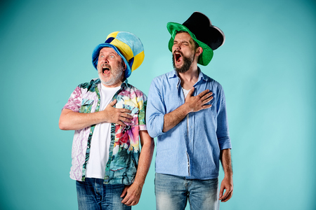 anthem: The two football fans singing the national anthem over blue background Stock Photo