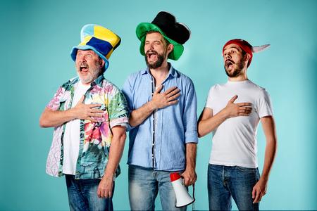 青い背景に国歌を歌う 3 つのフットボールのファン