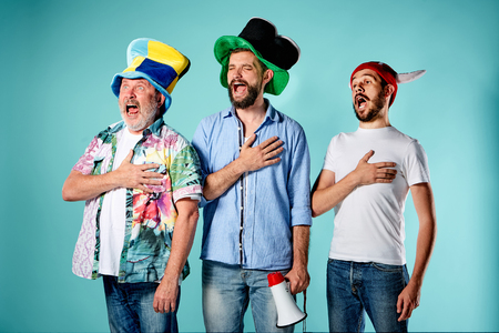 anthem: The three football fans singing the national anthem over blue background Stock Photo