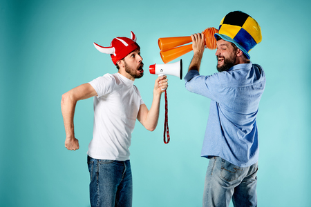 the admirer: The two football fans with mouthpiece over blue background