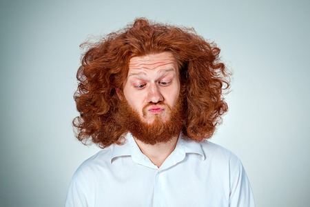 disgusted: The portrait of disgusted man with long red hair Stock Photo