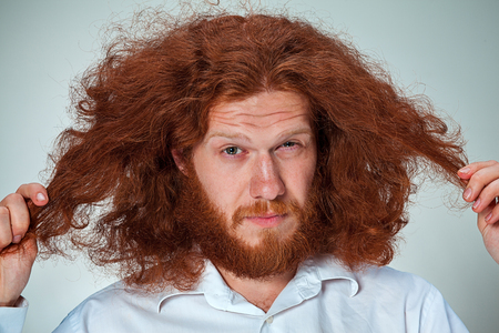 screwing: The young man with long red hair looking at camera, screwing up his eyes Stock Photo