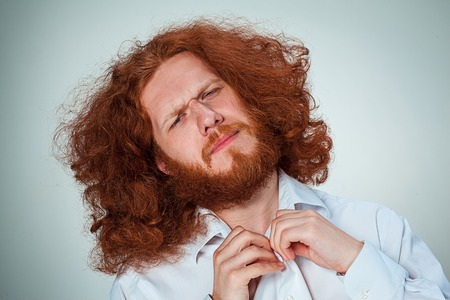 squinting: The young man with long red hair looking at camera squinting