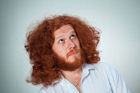 looking aside: The young man with long red hair looking aside in thought