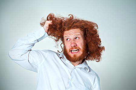tearing: The angry young man with long red hair tearing his hair