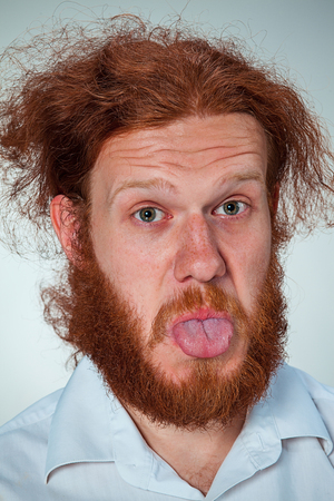 is disgusted: The portrait of disgusted man with long red hair Stock Photo