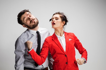 conflicting: The funny angry business man and woman conflicting on a gray background. Business concept of relationship of colleagues