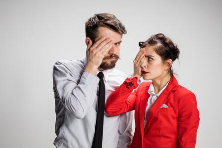 cerrando negocio: El hombre de negocios y la mujer sobre un fondo gris cerrando un ojo con la mano