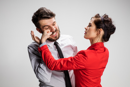 conflicting: The business man and woman conflicting on a gray background. Business concept of relationship of colleagues