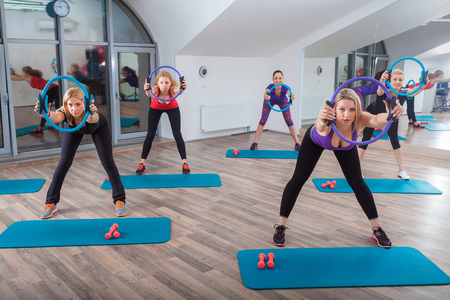 women working out: fitness, sport, training and lifestyle concept - group of women working out in gym