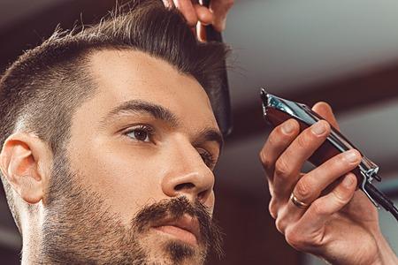 Le mani di giovane making barbiere taglio di capelli di attraente uomo barbuto in piccolo coro polifonico
