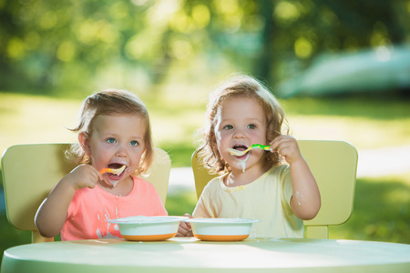 2 years old: Two little 2 years old girls sitting at a table and eating together against a green lawn Stock Photo