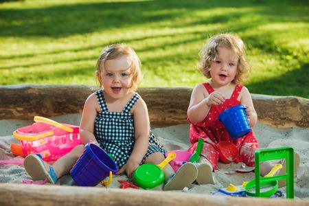 Die beiden kleinen Baby Mädchen zwei Jahre alte Spiel Spielzeug in Sand gegen grüne Gras