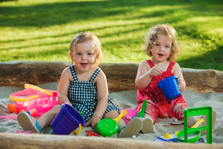 The two little baby girls two-year old playing toys in sand against green grass