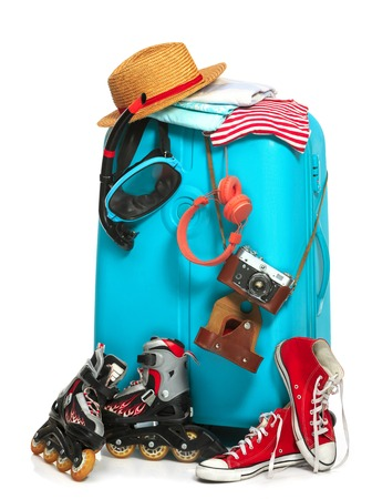 The blue suitcase, sneakers, clothing, hat, and retro camera on white background. The travel, tourism and holidays concept Stock Photo