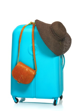 The modern large blue suitcase and woman hat and bag on a white background Stock Photo