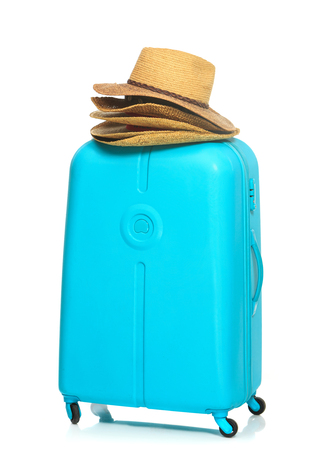 lugage: The modern large blue suitcase and many hats on a white background. The travel, tourism and holidays concept Stock Photo