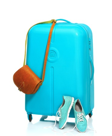 The blue suitcase, sneakers, handbag on white background. The travel, tourism and holidays concept