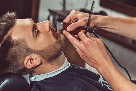Hipster cliente visitando barbería. Las manos del joven barbero que pasan el corte de la barba Foto de archivo - 60143825